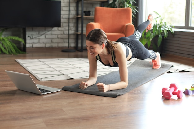 Piękna kobieta fitness robi ćwiczenie deski oglądając samouczki online na laptopie, trening w salonie. zdrowy tryb życia. dziewczyna uprawia sport w domu.