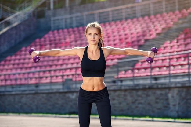 Piękna kobieta fitness z idealne ciało robi treningi z ultra fioletowe hantle na stadionie