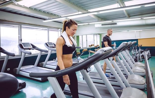 Piękna kobieta fitness z ręcznikiem na szyi, trening na bieżni w centrum fitness