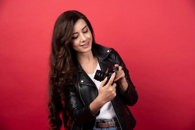 Piękna kobieta fotograf patrząc na aparat fotograficzny na czerwonym tle. zdjęcie wysokiej jakości