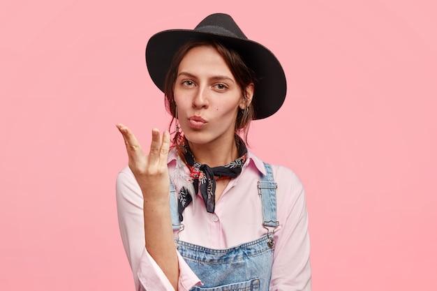 Piękna kobieta gestykuluje jak prawdziwy smak włoskiego makaronu, nie jadła czegoś smaczniejszego, ubrana w swobodne dżinsowe ogrodniczki, kapelusz, odizolowana na różowej ścianie. mmm, to wspaniale!