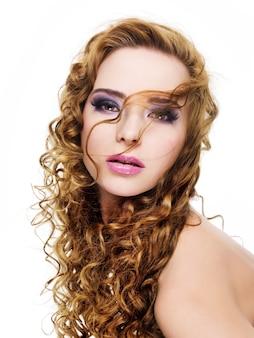 Piękna kobieta glamour z długie kręcone włosy i jasny stylowy fioletowy makijaż - na białym tle