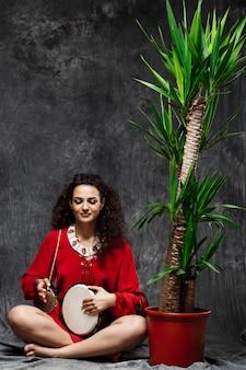 Piękna kobieta gra na bębnie w tropikalnych roślin na szarej ścianie