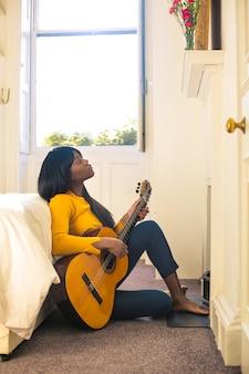 Piękna kobieta gra na gitarze, siedząc na podłodze w swojej sypialni