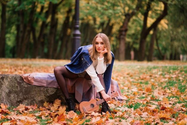 Piękna kobieta gra na gitarze ukulele na świeżym powietrzu w jesiennym lesie
