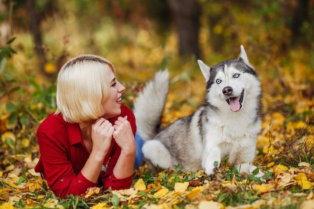 Piękna kobieta gra z psem husky w lesie jesienią