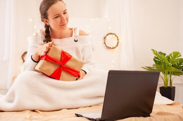 Piękna kobieta gratuluje swoim bliskim świąt bożego narodzenia przez łącze wideo.