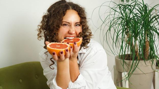 Piękna kobieta gryzie grejpfruta. kobieta w średnim wieku z kręconymi włosami w domu - jasny pokój. pojęcie szczęścia, piękna i zdrowia