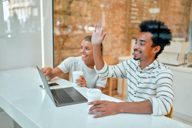 Piękna kobieta i atrakcyjny afrykanin piją kawę w kawiarni, pracują na laptopie, rozmawiają i bawią się.