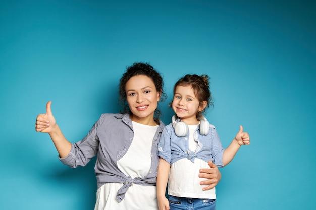 Piękna kobieta i córka jednakowo ubrane, pokazując kciuki do góry i uroczo uśmiechnięte, pozując do przodu na niebieskiej powierzchni z miejscem na kopię