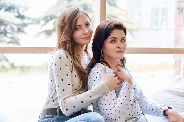 Piękna kobieta i córka, ufna pomyślna kobieta pozuje z córką