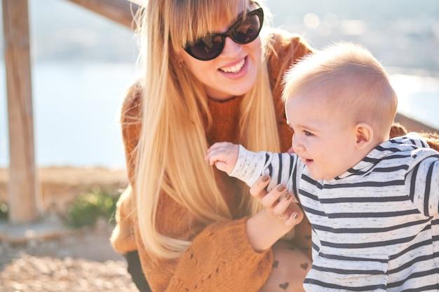 Piękna kobieta i jej śliczny synek bawią się i uśmiechają