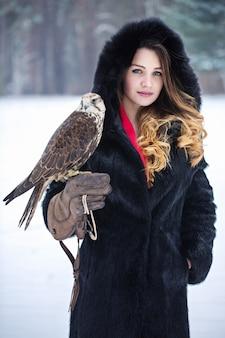 Piękna kobieta i sokół zimą