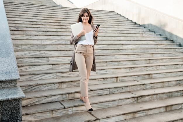 Piękna kobieta idąc po schodach z laptopa i telefonu