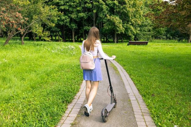 Piękna kobieta idzie ścieżką w parku i toczy swój elektryczny skuter