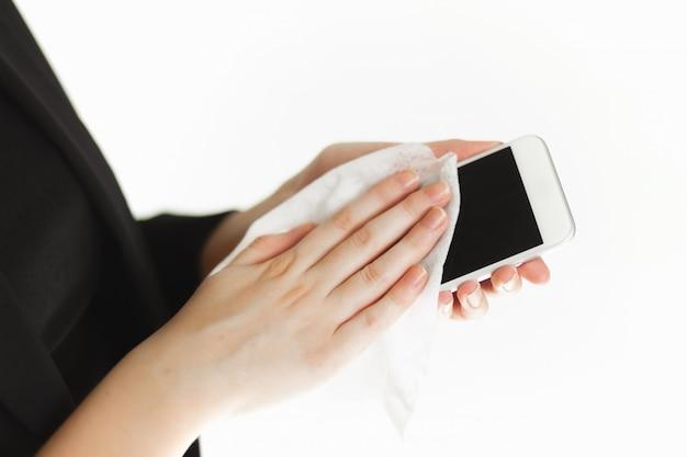 Piękna kobieta interesu w masce ochronnej wirusa medycznego czyści jej telefon chusteczkami antybakteryjnymi. środki ostrożności w przypadku pandemii. zamknij plan rozdania
