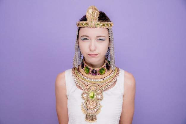 Piękna kobieta jak kleopatra w starożytnym egipskim stroju, mrużąc oczy z niezadowolenia na fioletowo