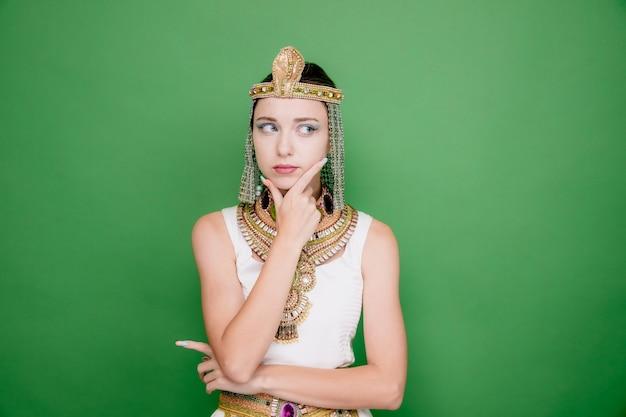 Piękna kobieta jak kleopatra w starożytnym egipskim stroju, patrząc na bok z zamyślonym wyrazem twarzy z ręką na brodzie, myśląc na zielono