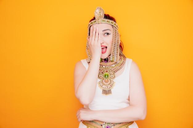 Piękna kobieta jak kleopatra w starożytnym egipskim stroju, patrząca na bok szczęśliwa i wesoła, zakrywająca jedno oko dłonią na pomarańczowo