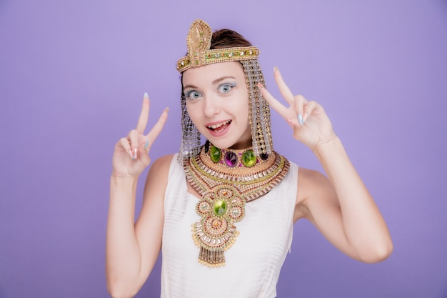 Piękna kobieta jak kleopatra w starożytnym egipskim stroju szczęśliwa i wesoła pokazująca znaki v uśmiechnięta radośnie na fioletowo