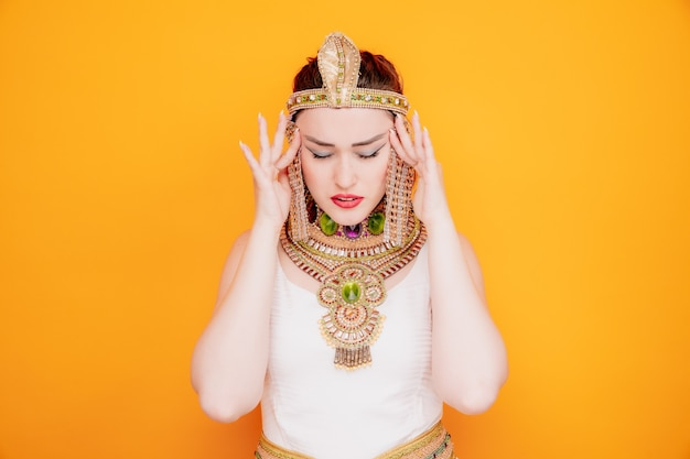 Piękna kobieta jak kleopatra w starożytnym egipskim stroju wyglądająca na zirytowaną i zirytowaną dotykając jej skroni cierpiących na ból głowy na pomarańczowy