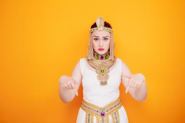 Piękna kobieta jak kleopatra w starożytnym egipskim stroju zdezorientowana, wskazując palcami wskazującymi w dół na pomarańczę