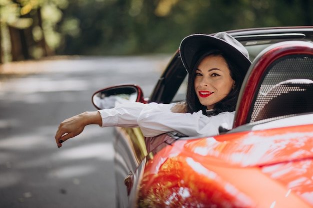 Piękna kobieta jazdy czerwonym cabrio