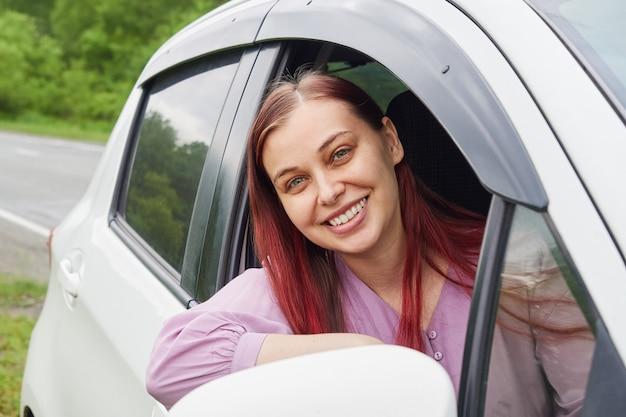 Piękna kobieta jazdy samochodem patrząc przez okno uśmiechając się patrząc w kamerę.