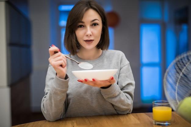 Piękna kobieta je jej śniadaniowych zboża w jej kuchni