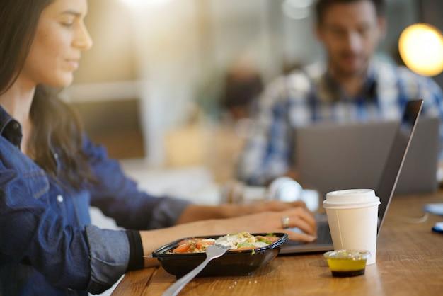 Piękna kobieta je lunch podczas pracy w przestrzeni roboczej