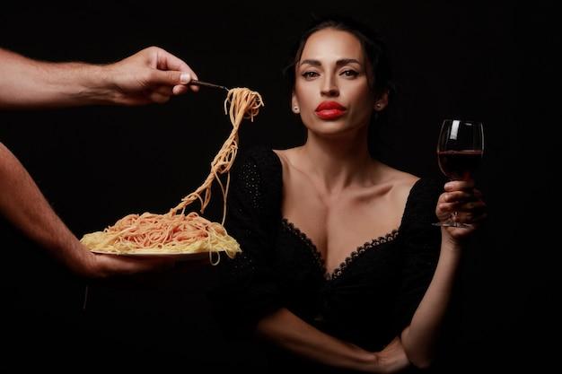 Piękna kobieta je spaghetti i pije wino