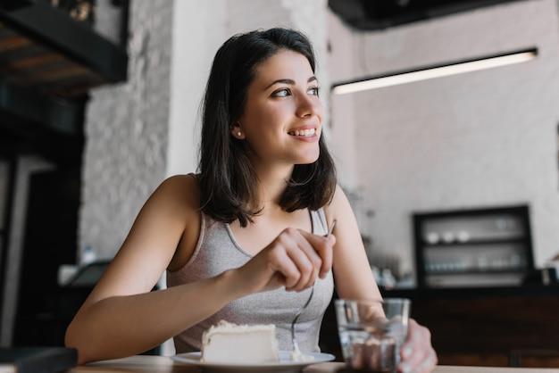 Piękna kobieta jedzenie sernik i wody pitnej w kawiarni. młoda pozytywna kobieta ma śniadanie