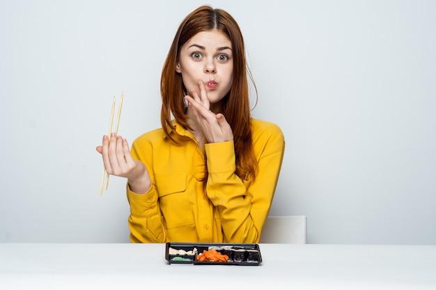 Piękna kobieta jedzenie sushi rolki pałeczkami