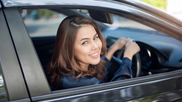 Piękna kobieta jedzie jej samochód