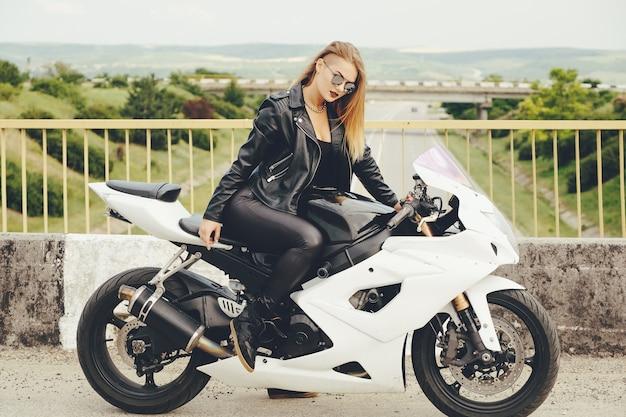 Piękna kobieta jedzie na motocyklu z okularami przeciwsłonecznymi