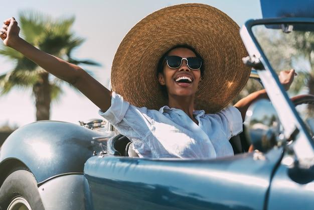 Piękna kobieta jedzie rocznika kabrioletu samochód