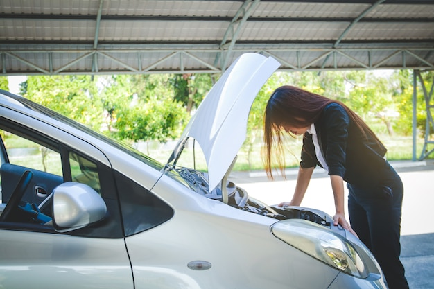 Piękna kobieta, jej samochód jest zepsuty podczas gdy ona spieszyła się do pracy w biurze