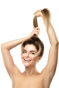 Piękna kobieta jest bardzo zadowolona z postępów wzrostu włosów. odosobniony.