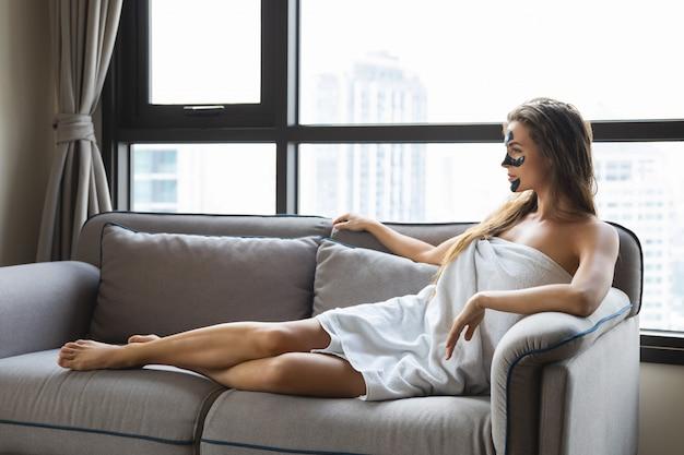 Piękna kobieta jest relaksująca w domu z czarną maską peel-off na twarzy