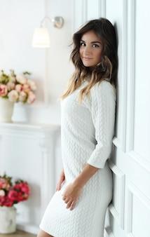 Piękna kobieta jest ubranym biel suknię w białym pokoju