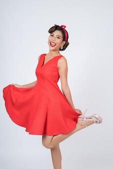 Piękna kobieta jest ubranym czerwieni suknię w studiu