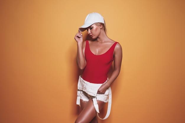 Piękna kobieta jest ubranym czerwonego swimsuit i baseball nakrętkę pozuje na kolorze żółtym