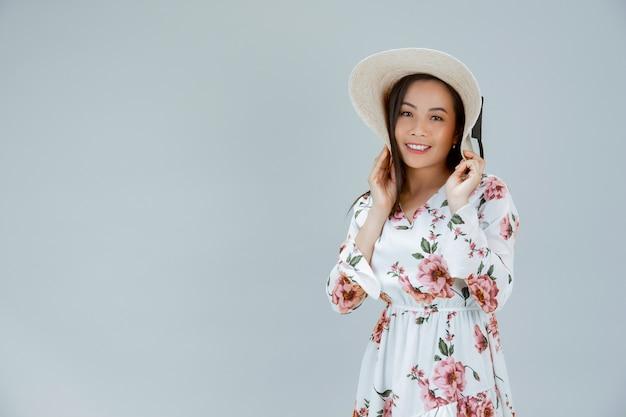 Piękna kobieta jest ubranym kwiecistą suknię