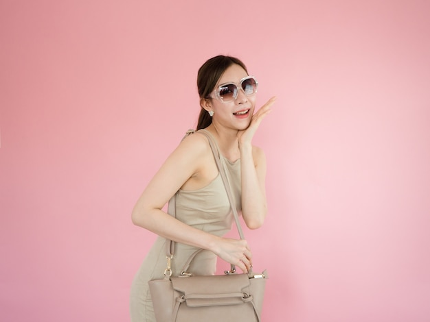 Piękna kobieta jest ubranym okulary przeciwsłonecznych i niesie rzemienne torby, mody pojęcie