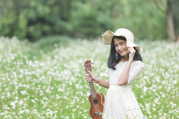 Piękna kobieta jest ubranym śliczną białą suknię i trzyma ukulele