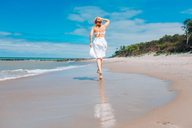 Piękna kobieta jest ubranym słomianego kapelusz, biały strój kąpielowy i spódnicy odprowadzenie wzdłuż kipieli linii na plażowych pobliskich fala.