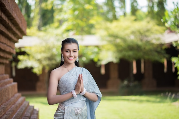 Piękna kobieta jest ubranym typową tajlandzką suknię