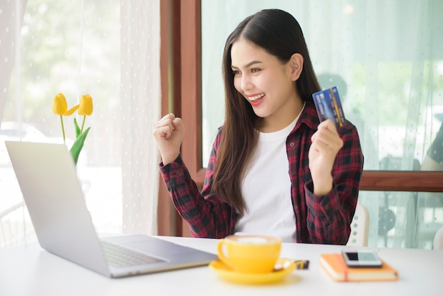 Piękna kobieta jest zakupy online kartą kredytową w kawiarni