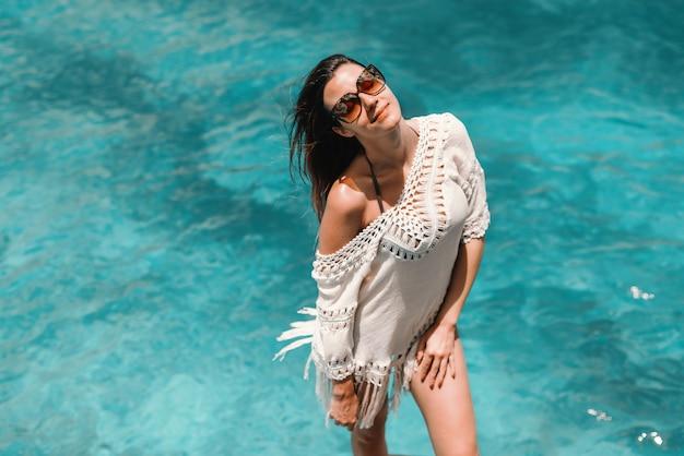 Piękna kobieta kaukaski z brązowymi włosami i okulary przeciwsłoneczne, pozowanie na plaży.