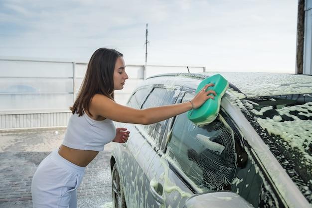 Piękna kobieta kierowca mycia przedniej szyby z gąbką w czystej pianie na jej brudnym samochodzie na stacji ręcznej